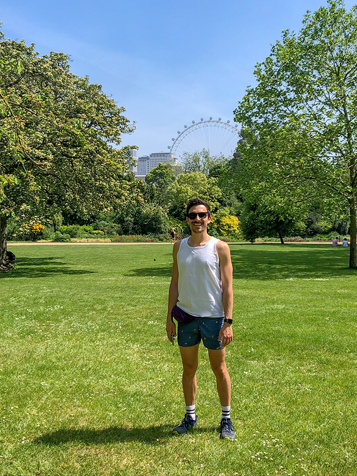 A picture of Luke standing in a green open space of St Jame Park in London with a glimpse of the London eye in the distant background