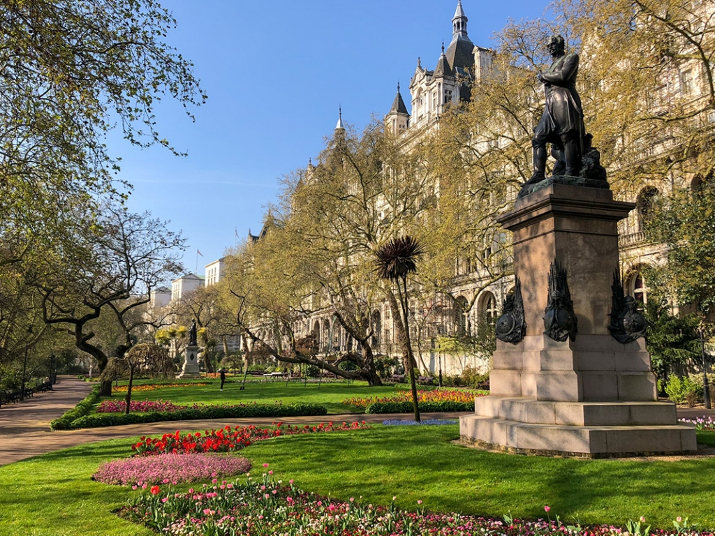 The green and vibrant gardens of the Victoria Embankment Gardens located in London. The park is aligned by trees and a statue is visible to the right of the photograph