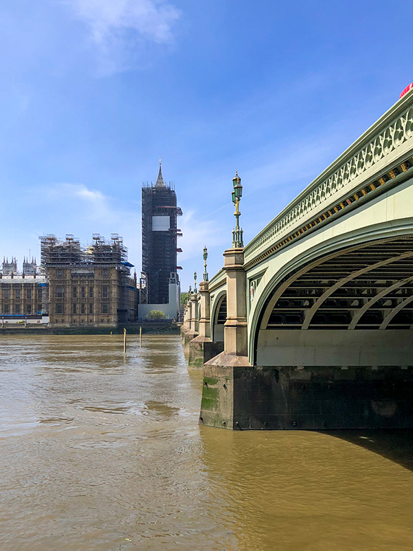 A blue sky over Westminster Bridge, London to the right with Big Ben (Elizabeth Tower) in the background.