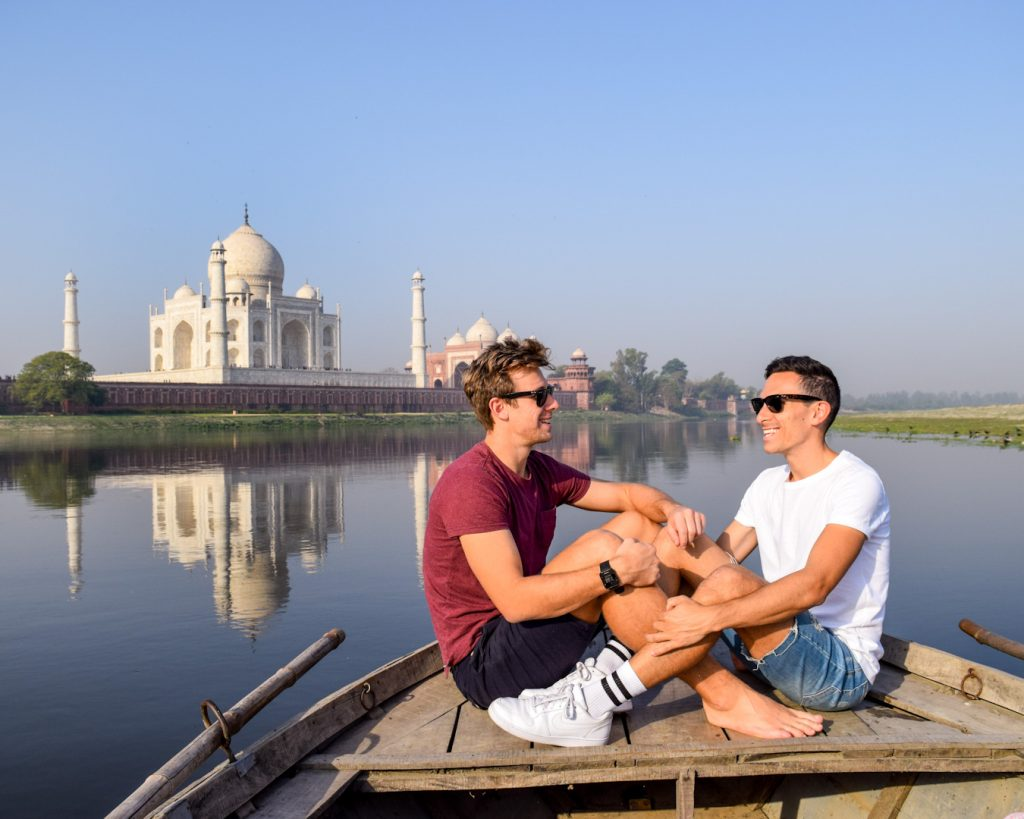 Luke and Craig sitting in a boat infront of the Taj Mahal in India