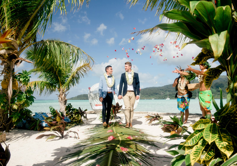 Luke and Craig walking down a palm tree lined isle with Polynesian dancers throwing rose petals on us.